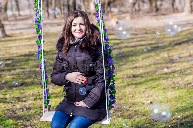 Mujer embarazada hermosa que toca su vientre con las manos fotos de archivo