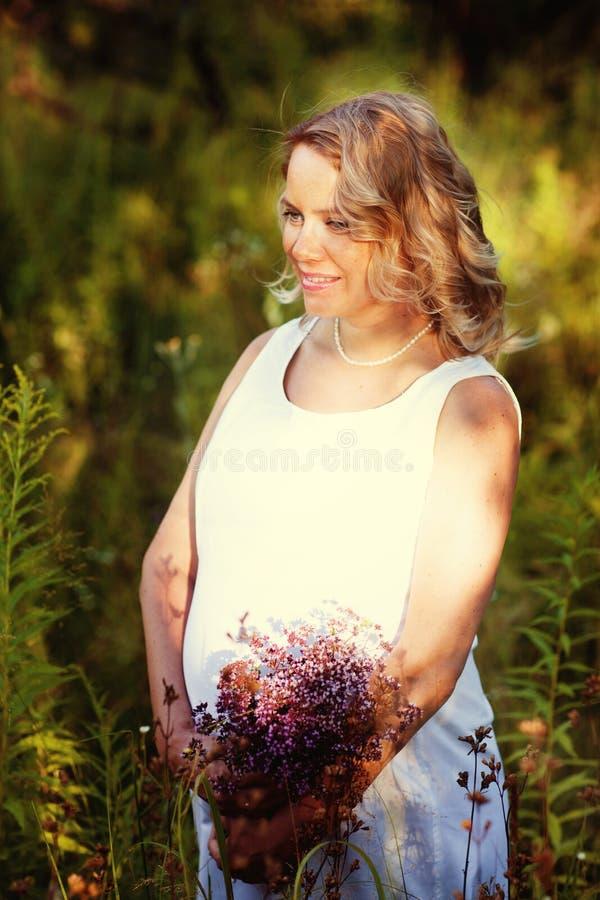 Mujer embarazada hermosa y feliz en un vestido blanco en la naturaleza en el verano, alrededor de los árboles y de las flores foto de archivo libre de regalías