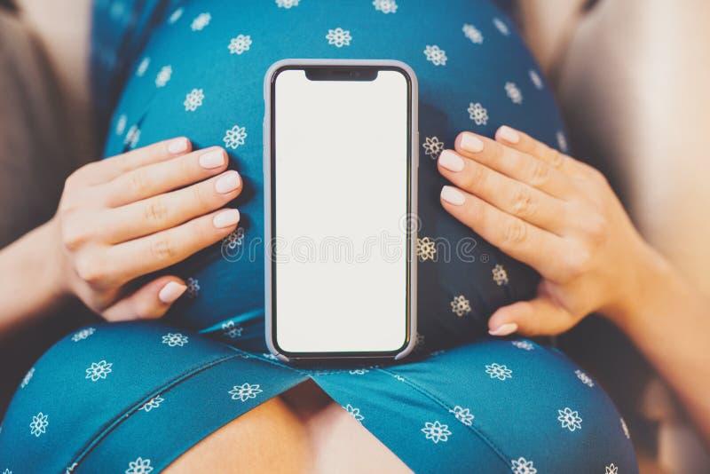 Mujer embarazada irreconocible que se sostiene el vientre Teléfono móvil con la pantalla vacía Copie el espacio fotografía de archivo libre de regalías