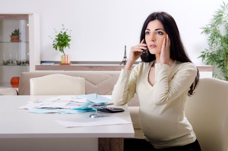 Mujer embarazada joven en concepto del planeamiento del presupuesto fotos de archivo libres de regalías