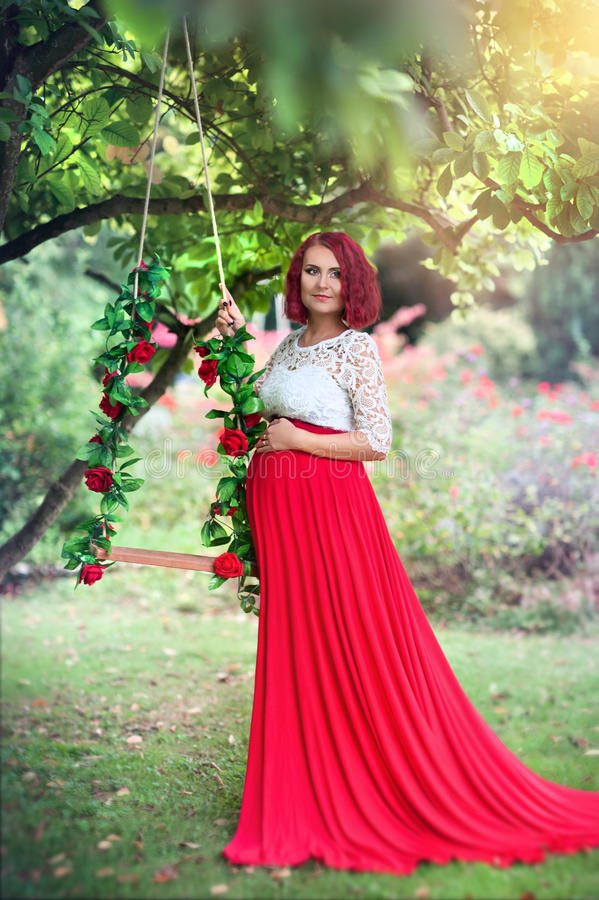 Mujer embarazada joven hermosa que se coloca en el jardín foto de archivo