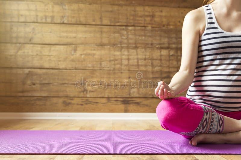 Mujer embarazada joven hermosa que se sienta en la posición de loto respecto a la estera de la yoga fotografía de archivo libre de regalías