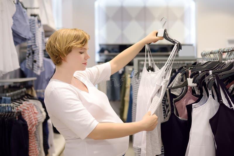Mujer embarazada joven que elige la ropa interior para amamantar en tienda imagenes de archivo