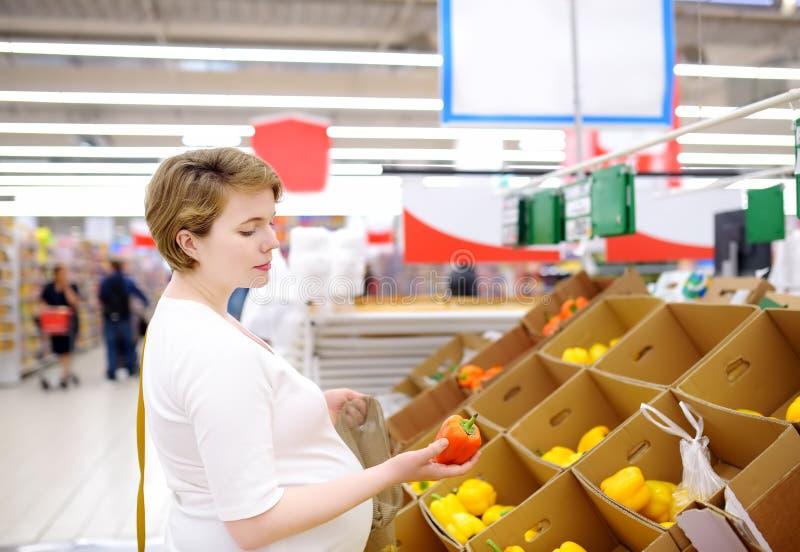 Mujer embarazada joven que elige las frutas y verduras en bolso de compras de la malla en supermercado foto de archivo