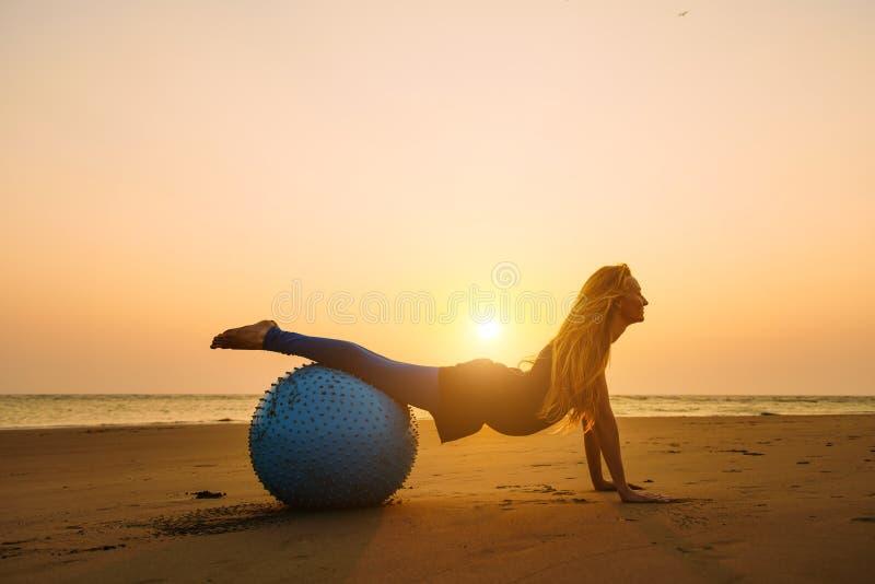 Mujer embarazada joven que estira en bola de entrenamiento contra puesta del sol sobre el mar Belleza y salud durante embarazo Yo imágenes de archivo libres de regalías