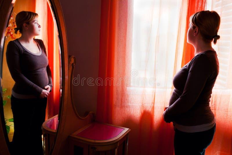 Mujer embarazada pensativa imagen de archivo
