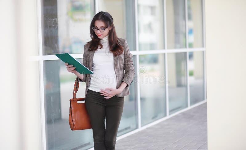 Mujer embarazada que camina en la calle fotos de archivo