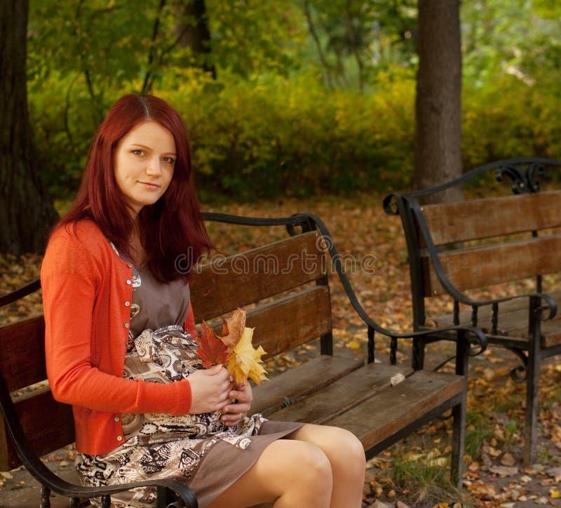 Mujer embarazada que camina en parque del otoño foto de archivo