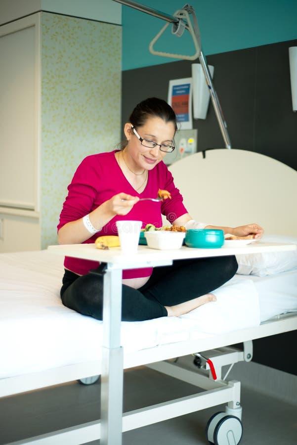 Mujer embarazada que come la comida en sala de hospital fotos de archivo