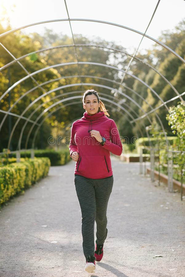 Mujer embarazada que corre en otoño foto de archivo