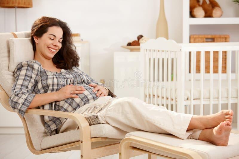 Mujer embarazada que descansa en butaca en cuarto de niños imagenes de archivo