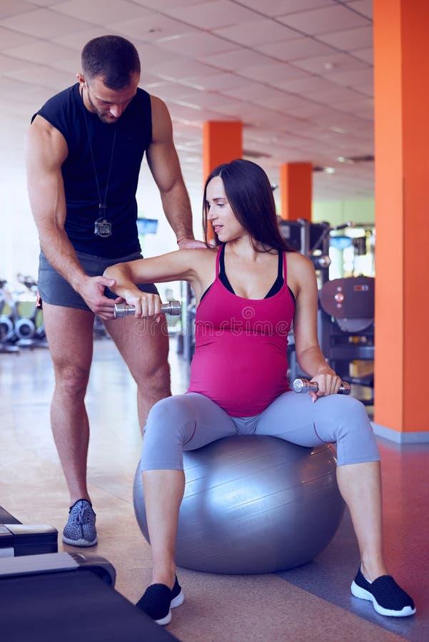 Mujer embarazada que ejercita con el instructor personal en gimnasio fotos de archivo