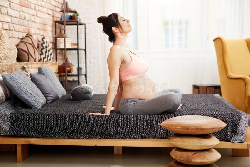Mujer embarazada que ejercita la relajación en casa imagenes de archivo