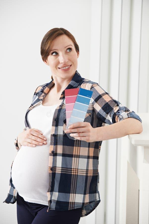 Mujer embarazada que elige el esquema de color para el sitio del bebé imagen de archivo libre de regalías