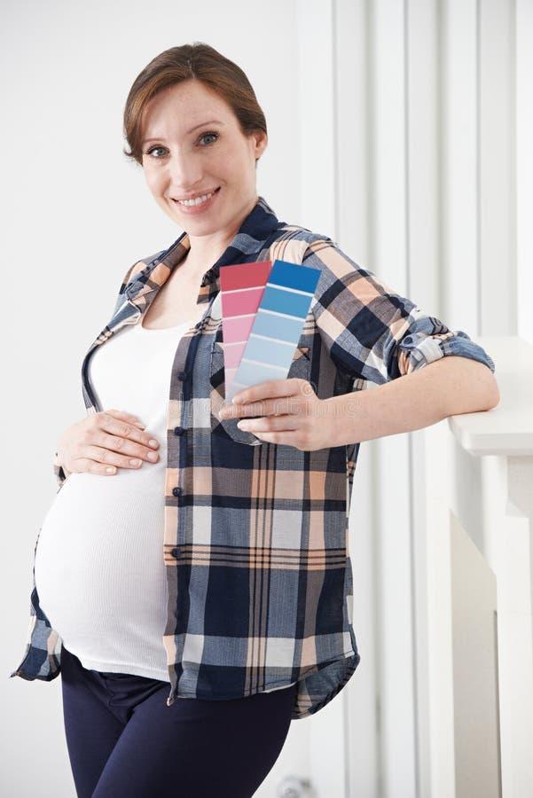 Mujer embarazada que elige el sitio del bebé del fuerte del esquema de color foto de archivo libre de regalías