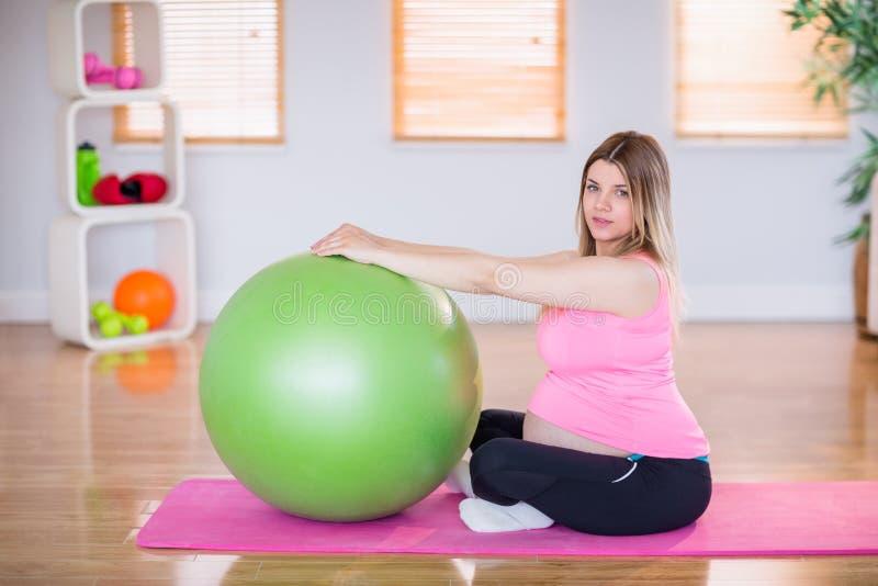 Mujer embarazada que hace ejercicio con la bola del ejercicio fotografía de archivo libre de regalías