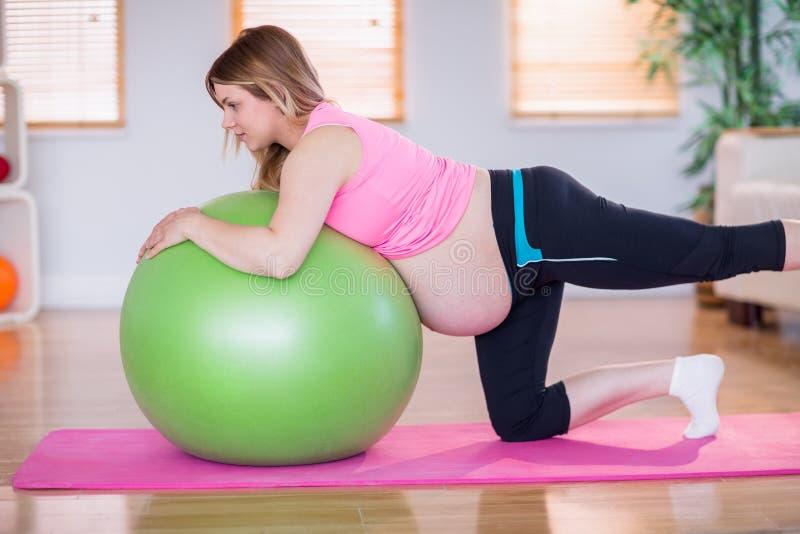 Mujer embarazada que hace ejercicio con la bola del ejercicio foto de archivo