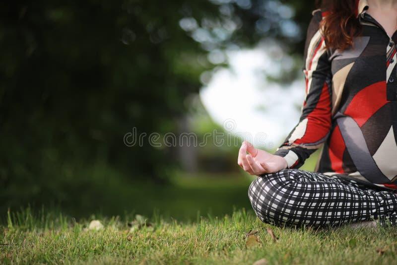 Mujer embarazada que hace ejercicio de la yoga en naturaleza imagenes de archivo