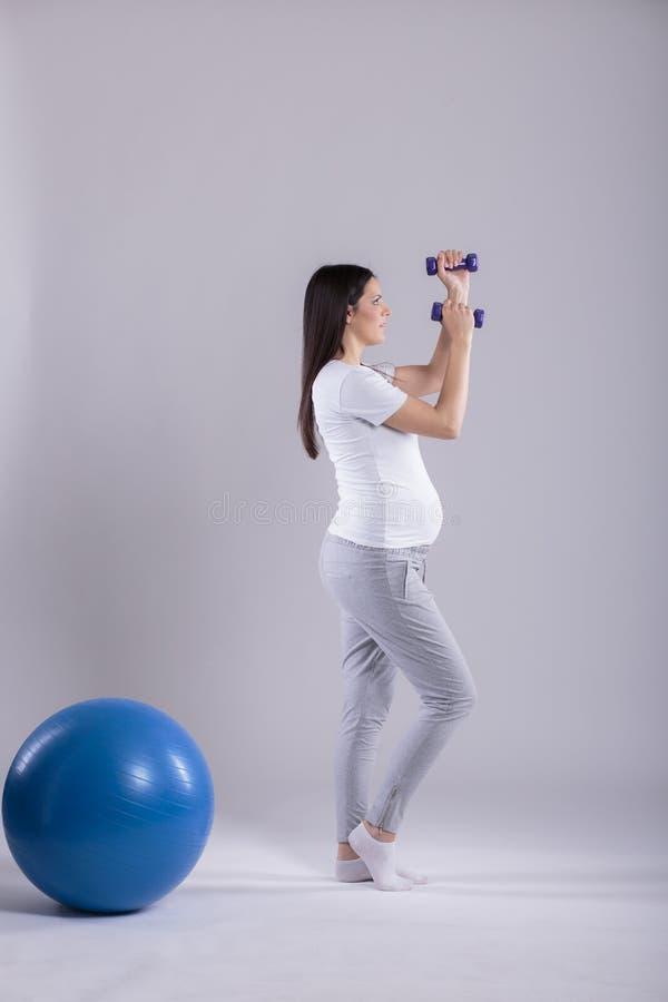 Mujer embarazada que hace ejercicios fotos de archivo libres de regalías