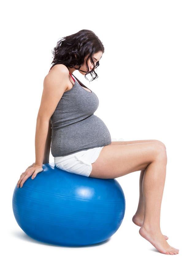 Mujer embarazada que hace ejercicios de los pilates fotografía de archivo