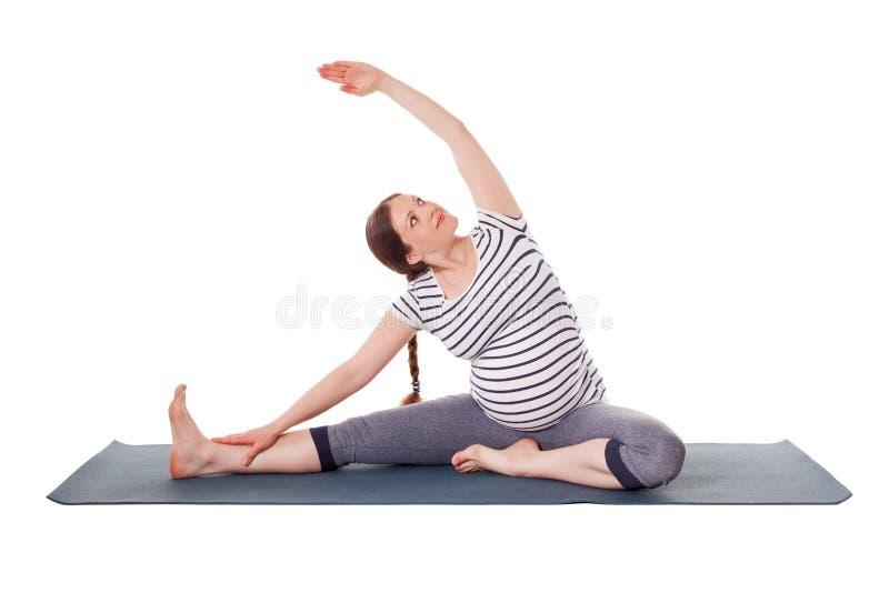 Mujer embarazada que hace sirsasana del janu de Parivrtta del asana de la yoga foto de archivo libre de regalías