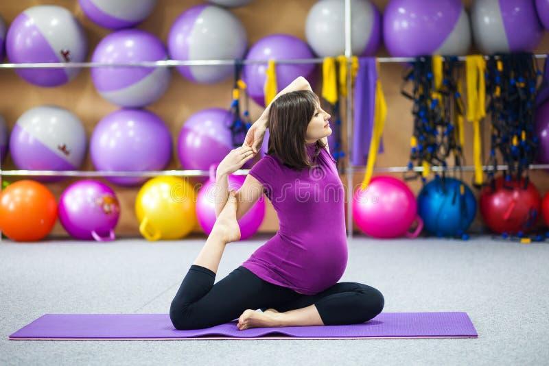 Mujer embarazada que hace yoga fotos de archivo libres de regalías