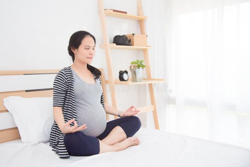 Mujer embarazada que hace yoga en el país imagen de archivo libre de regalías