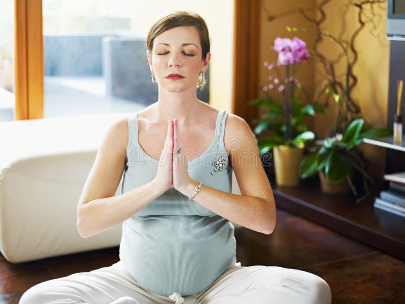 Mujer embarazada que hace yoga en el país imágenes de archivo libres de regalías
