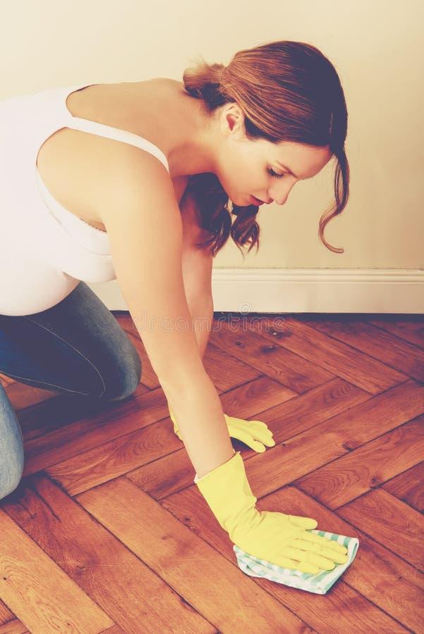Mujer embarazada que limpia en casa fotos de archivo