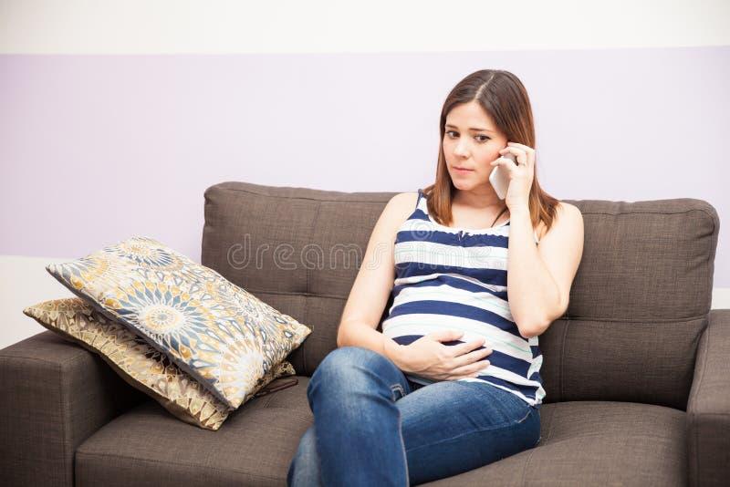 Mujer embarazada que llama a su doctor imagen de archivo libre de regalías