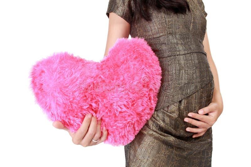 Mujer embarazada que lleva un amor muñeca-formado imagenes de archivo