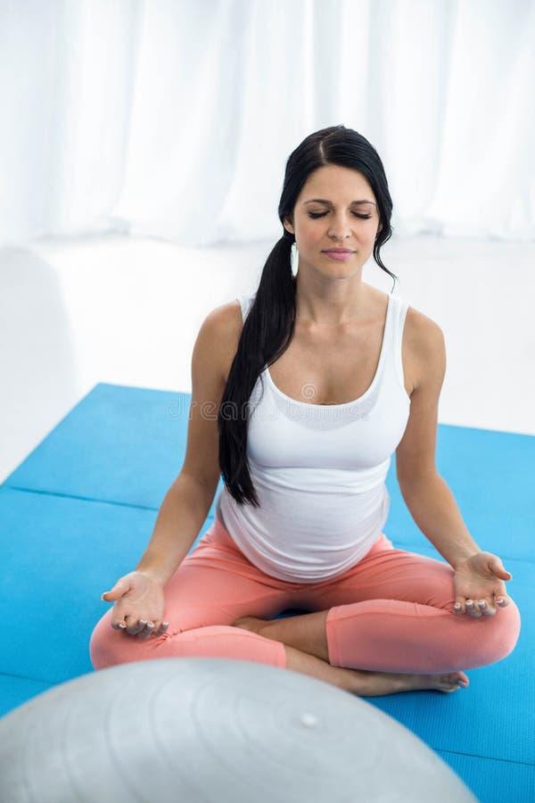 Mujer embarazada que medita en la posición de loto imagen de archivo libre de regalías