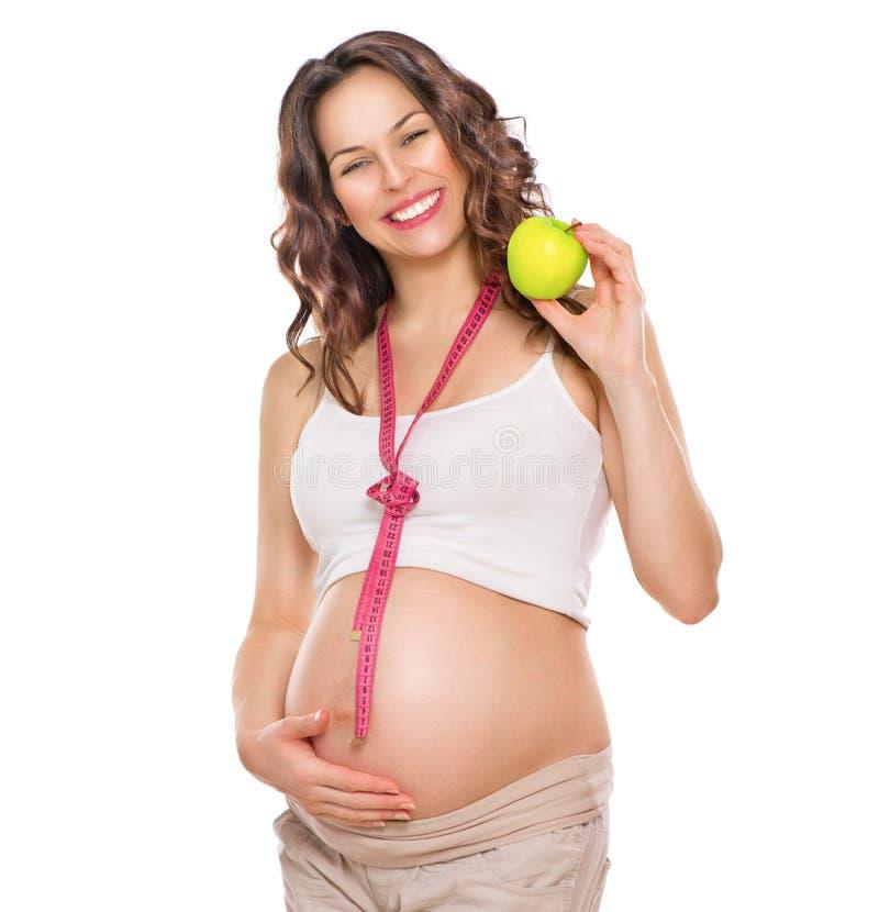 Mujer embarazada que mide su vientre grande y que come la manzana fotos de archivo libres de regalías