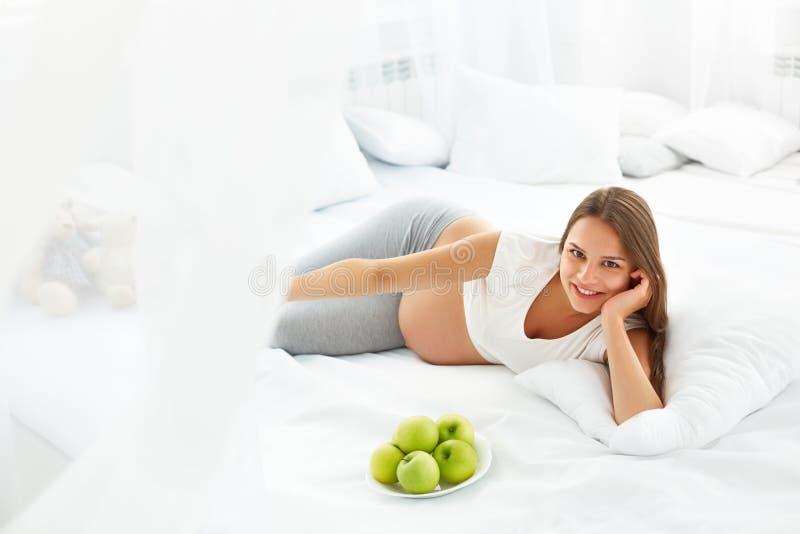 Mujer embarazada que miente en la cama con las manzanas frescas Alimento sano imagenes de archivo