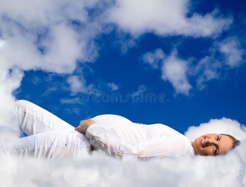 Mujer embarazada que miente en las nubes foto de archivo