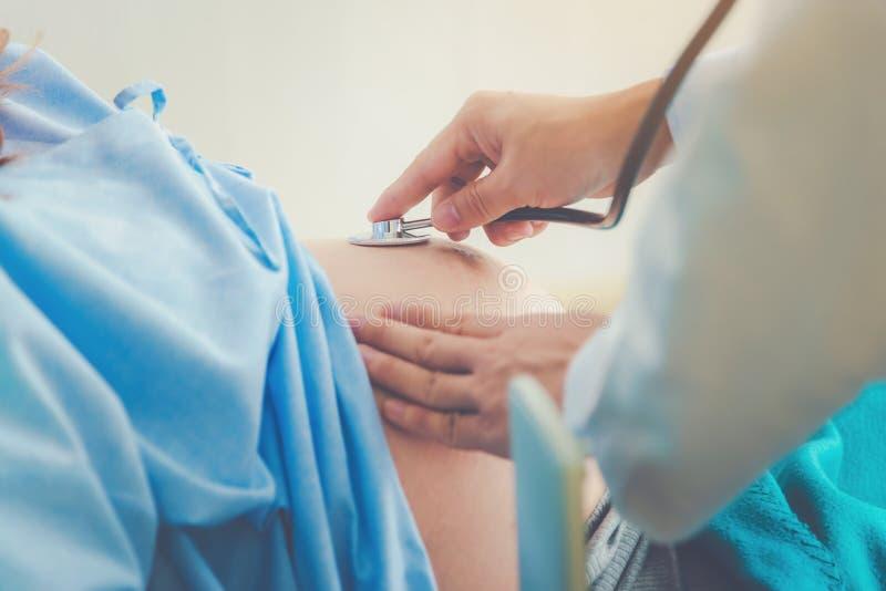 Mujer embarazada que miente en parto que espera de la cama para con la supervisi?n m?dica en un hospital fotos de archivo libres de regalías