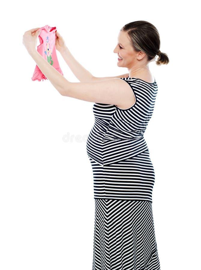 Mujer embarazada que mira el paño del bebé, disfrutando foto de archivo