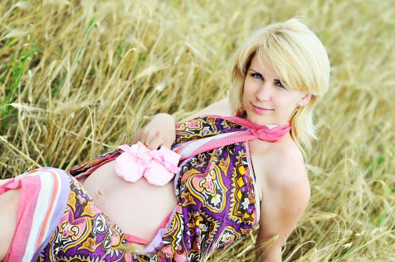Mujer embarazada que pone en campo de trigo foto de archivo