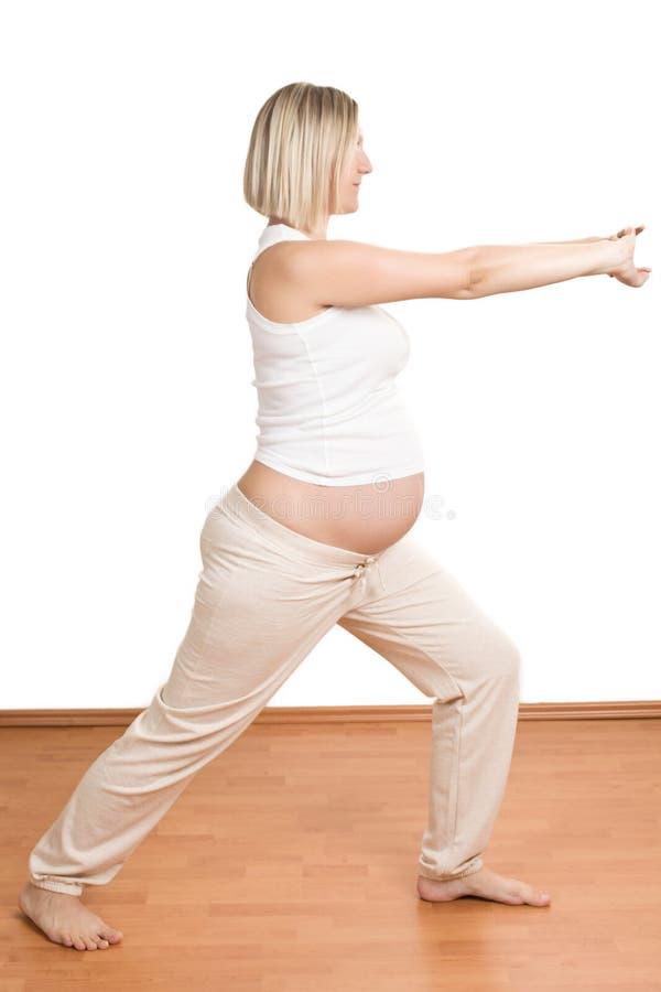 Mujer embarazada que practica ejercicio físico fotos de archivo
