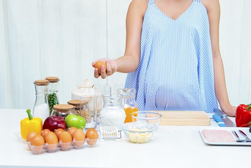 Mujer embarazada que prepara la comida en la tabla en la cocina, NU sano foto de archivo