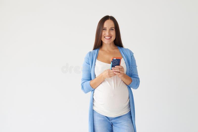 Mujer embarazada que presenta con el teléfono contra el fondo blanco fotos de archivo