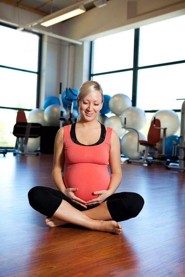 Mujer embarazada que relaja y que sostiene el vientre. imagenes de archivo