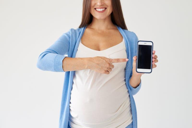 Mujer embarazada que señala en el smartphone con la pantalla negra imagenes de archivo