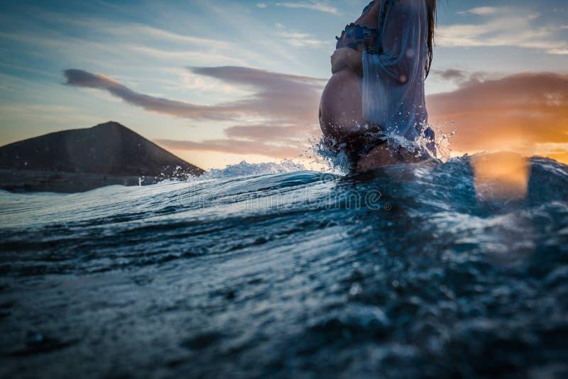 Mujer embarazada que se baña en el mar fotos de archivo