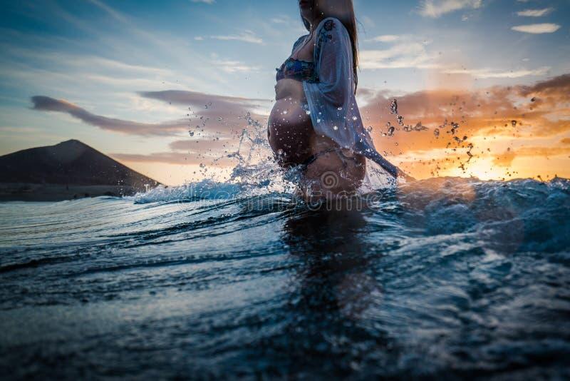 Mujer embarazada que se baña en el mar foto de archivo
