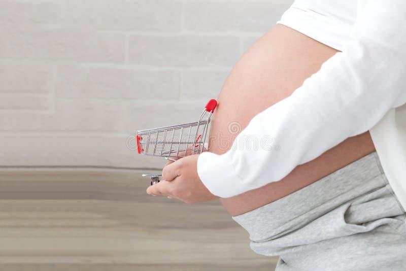 Mujer embarazada que se prepara para comprar productos del bebé antes del nacimiento, sosteniendo el carro de la compra delante d imagenes de archivo