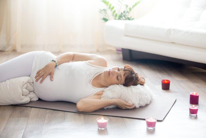 Mujer embarazada que se relaja después de práctica de la yoga en actitud del cadáver en ho foto de archivo