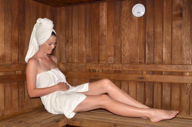 Mujer embarazada que se relaja en sauna imagenes de archivo