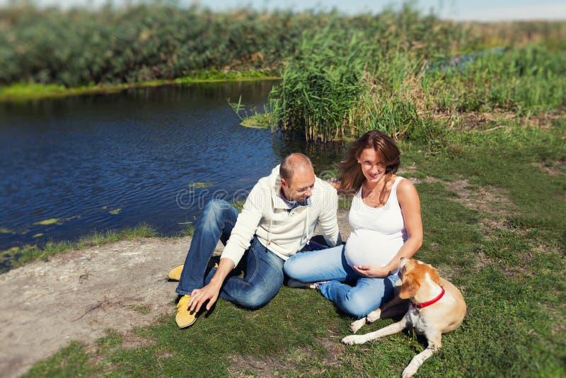 Mujer embarazada que se sienta cerca de su marido y perro foto de archivo