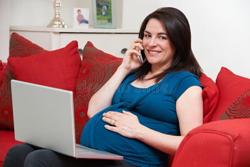 Mujer embarazada que se sienta en el teléfono de Sofa Using Laptop And Mobile fotos de archivo libres de regalías